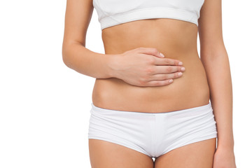 Mid section of slim woman touching her belly with one hand