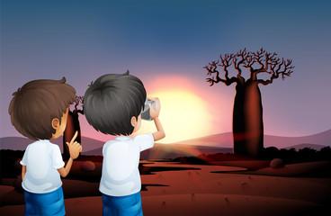 Two boys taking photos at the desert