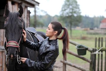 Piękna dziewczyna przygotowuje konia do jazdy,
