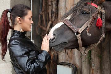 Piękna dziewczyna pieści łeb konia.