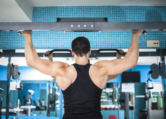 Rear view of young bodybuilder training his back