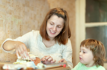 Happy mother with girl cookis in kitchen
