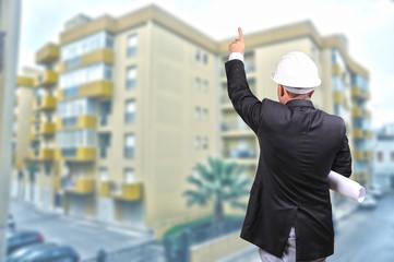 Bauarbeiter mit Planrolle deutet auf hochhaus