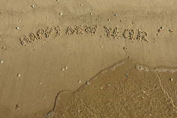 Inscription Happy new year on the sand
