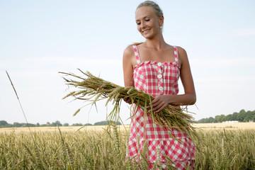 Blonde Frau geht durch ein Getreidefeld