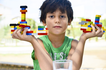 Boy in the park showing his brick construction