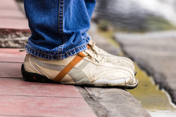 Ripped shoes, waiting someone at a bus stop in Bangkok, Thailand