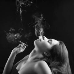 Woman smoking cigar against dark background. Black and white stu