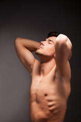 young muscular man with a bare chested on black.