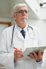 Doctor holding patient file and looking up