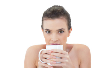 Shy natural brown haired model holding a mug of coffee