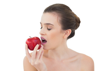 Relaxed natural brown haired model biting an apple