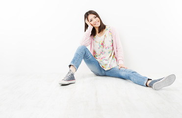 Young woman teenager in jeans sitting on white floor