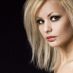 Fashion blonde girl with makeup and hairstyle over black