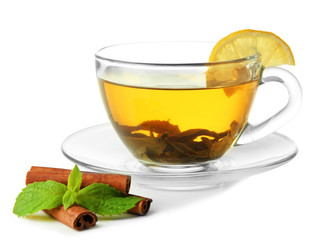 Transparent cup of green tea with cinnamon and mint isolated