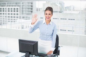Cheerful brunette businesswoman waving