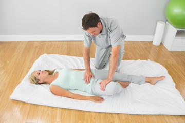 Physiotherapist treating patient on a mat on the floor