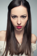 Portrait of angry beautiful long-haired brunette posing