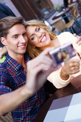 Young couple taking picture of themselves in summer cafe