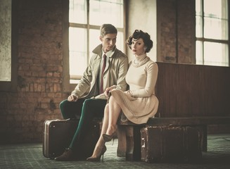 Beautiful vintage style young couple with suitcases