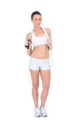 Pretty fit sportswoman holding skipping rope around neck