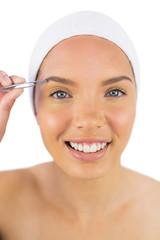 Smiling woman wearing headband using tweezers