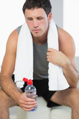 Sporty exhausted man holding water bottle