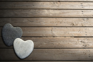 Stone Hearts on Wooden Boardwalk with Sand