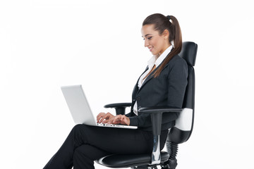 Smiling businesswoman sitting in a chair with laptop.