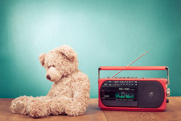 Retro toy Teddy Bear and radio recorder in front mint green