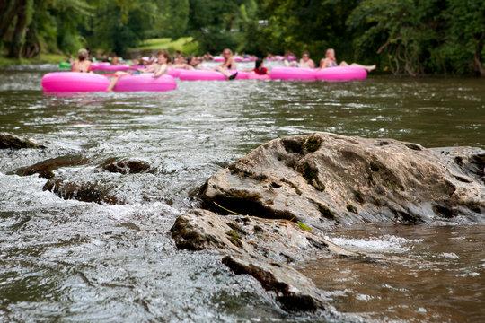Defocused People Tubing Down River Approach Boulder In Focus