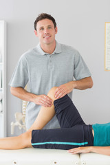 Smiling physiotherapist controlling knee of a patient