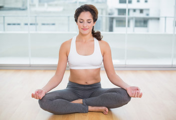 Sporty content brunette sitting in lotus pose with eyes closed