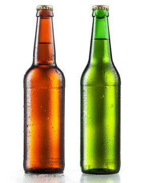 Bottles of beer with water drops on white background