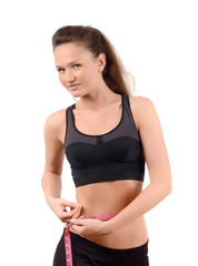 Girl measuring her waist with a measuring tape in centimeters