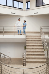Nurse and doctor talking at top of stairwell