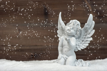 little white angel with magic lights in snow