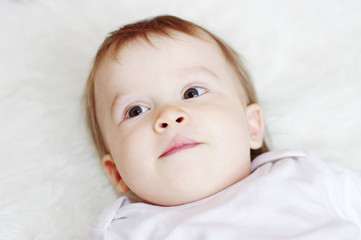 portrait of lovely baby lying on white bed
