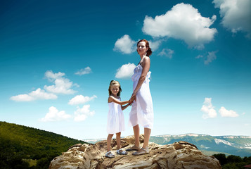 Mother and daughter on the top of mountain, looking on the beaut