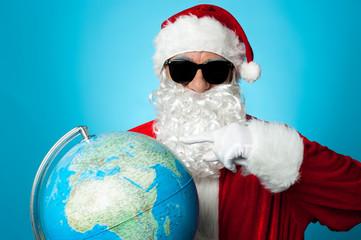 Santa pointing at globe map