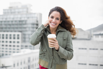 Happy gorgeous brunette in winter fashion holding disposable cup