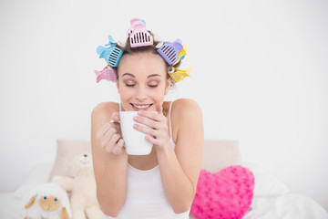 Funny natural brown haired woman in hair curlers enjoying coffee
