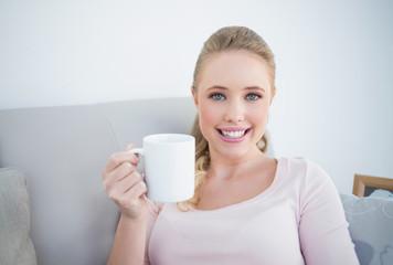 Casual gleeful blonde holding a mug