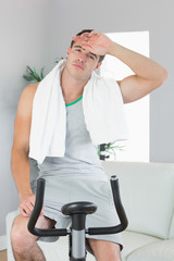 Tired handsome man exercising on exercise bike