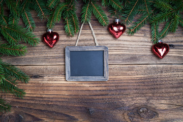 Pine tree with slate blackboard on old wooden background