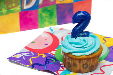 Birthday cupcake with blue icing and а candle