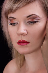 Portrait of a beautiful blonde girl with art make-up in studio