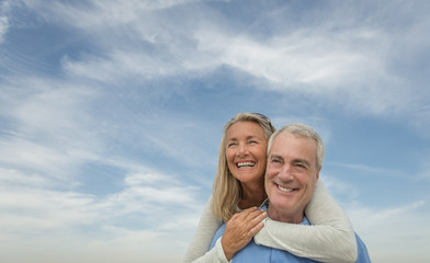 Senior Man Piggybacking Woman Against Cloudy Sky