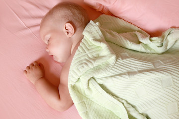 Little baby sleeps in the bed under soft green blanket