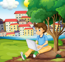 A young boy using the laptop under the tree at the riverbank